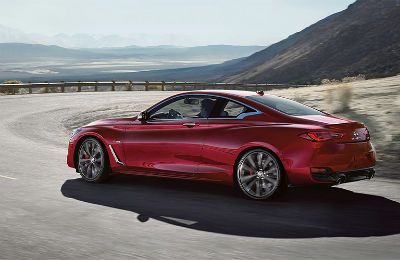 2020 Infiniti Q60 red exterior driver side rear fascia driving around curve