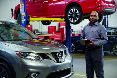 Nissan auto body shop technician holding clipboard and smiling
