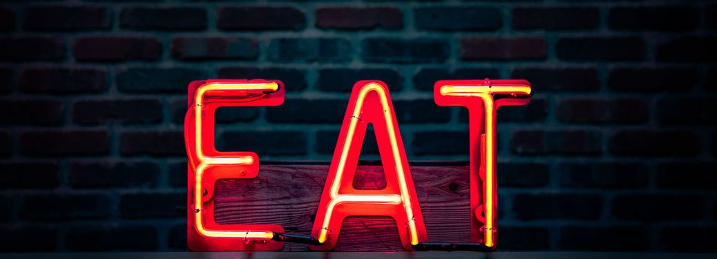red neon eat sign in front of dark brick wall
