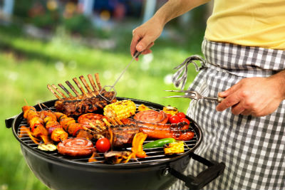 man cooking different meats and vegetables on a grill