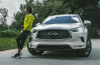 2020 Infiniti qx50 white exterior front  fascia woman leaning on front end
