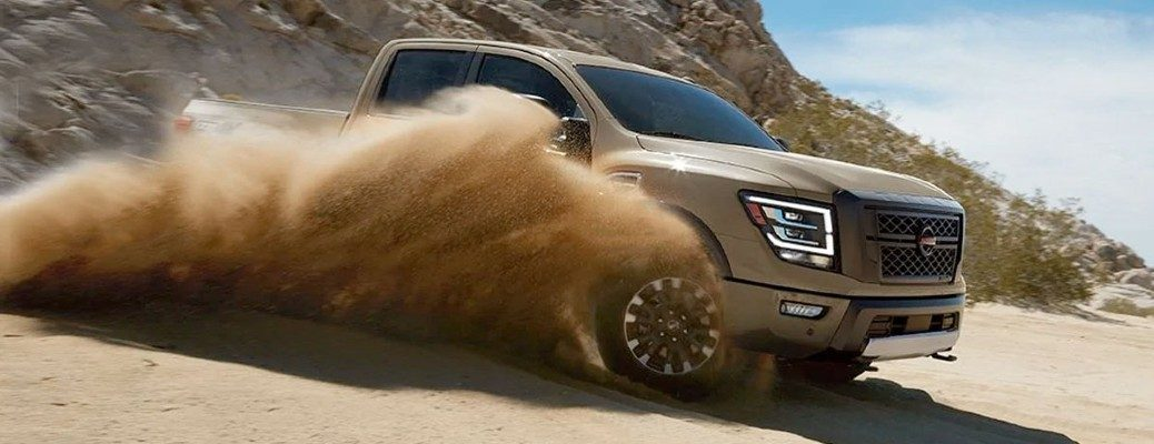 2020 Nissan Titan front passenger side driving through sand