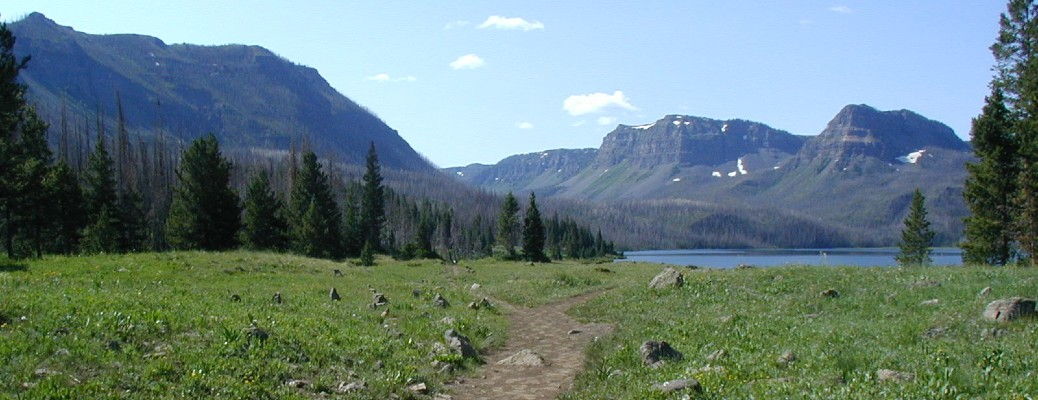 wilderness trail leading to lake and mountains