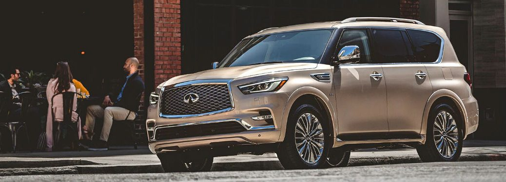 2020 Infiniti QX80 gold exterior front fascia driver side people sitting at table in background