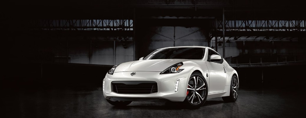 2020 Nissan 370Z exterior shot with Pearl White Tricoat paint color parked in a dark and empty hangar