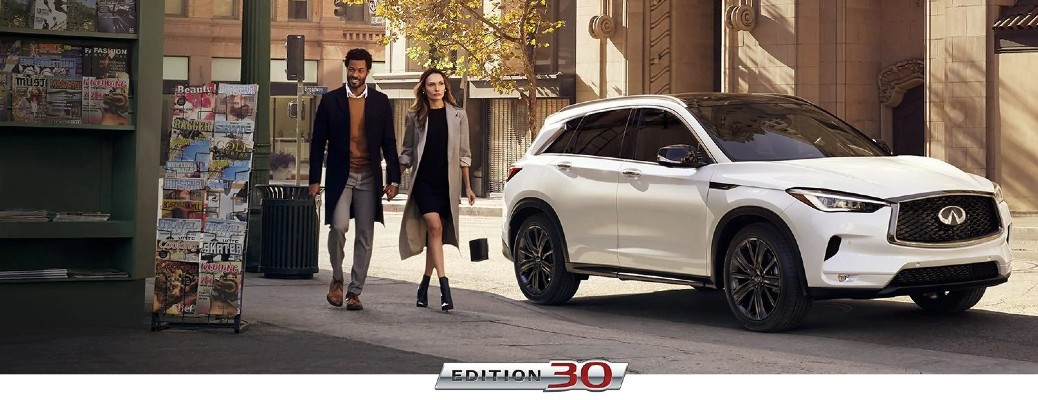 2020 INFINITI QX50 EDITION 30 promo shot as a couple walks down a city street past a magazine stand near the model