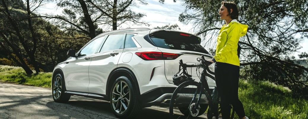 2020 INFINITI QX50 white back side view with woman and a bike