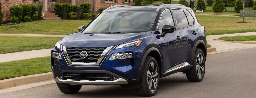 Blue 2021 Nissan Rogue driving on a residential street