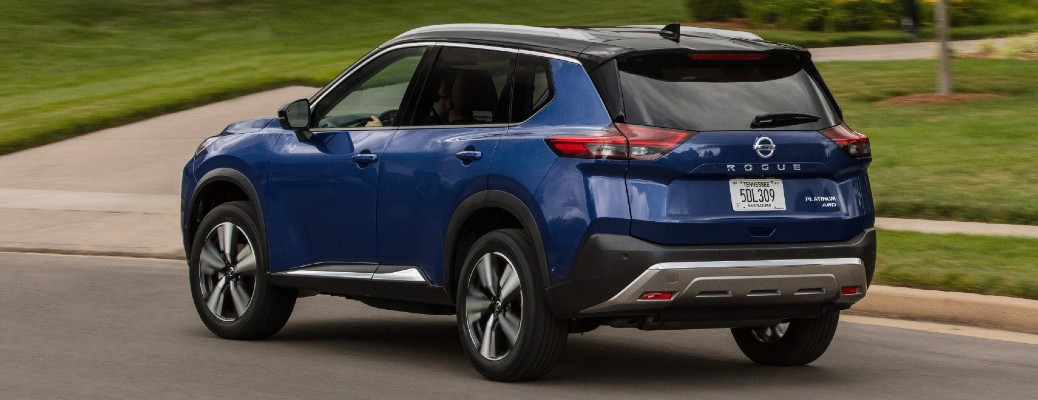 Driver's side rear angle view of blue 2021 Nissan Rogue