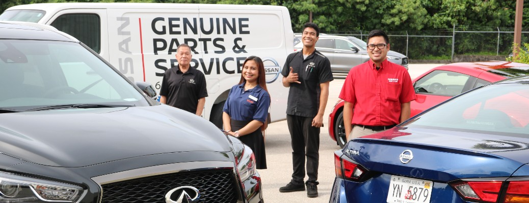 Nissan Guam employees standing in front of a Nissan service van
