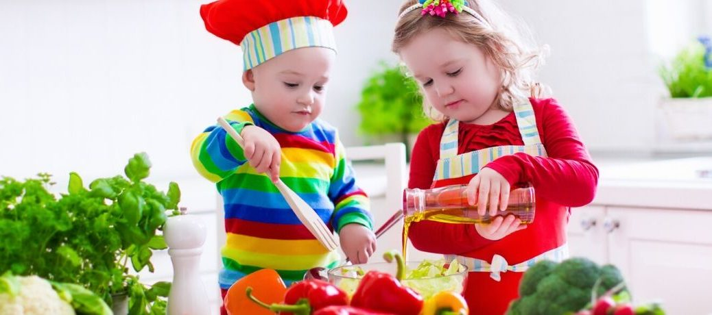 Kids in colorful clothing prepare a salad together