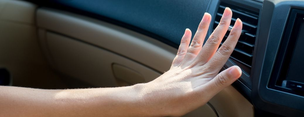 Hand feeling air coming out of car AC