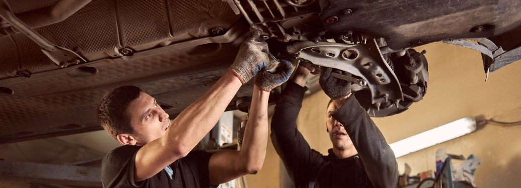 Technician and mechanic working on transmission