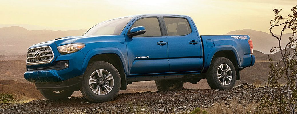 Blue Toyota Tacoma on hilltop overlooking desert sunset