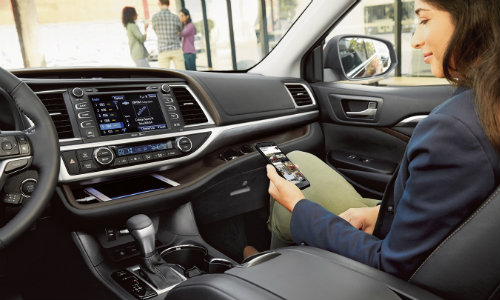 Woman connecting smartphone to Toyota Highlander EnTune system