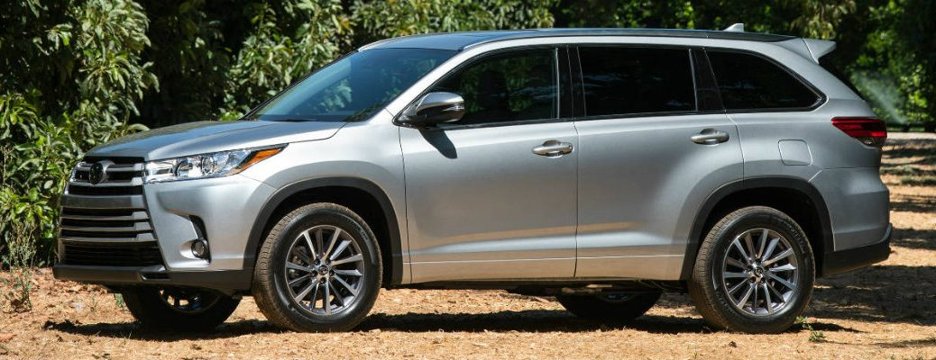 Profile view of silver 2018 Toyota Highlander parked in field with trees surrounding