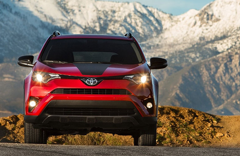 Front view of red 2018 Toyota RAV4 with mountains in background