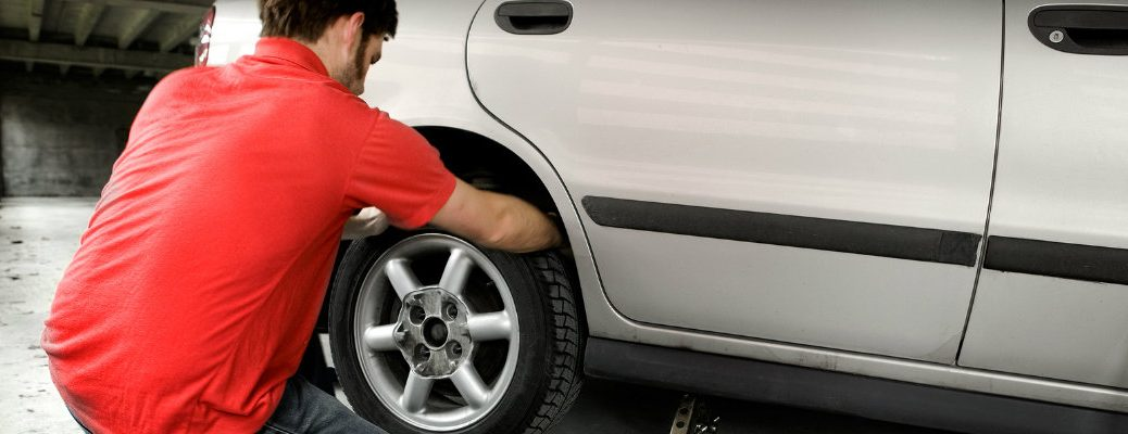 Man in automotive service shop changing a flat tire