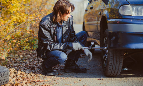 Man using wrench to change a flat tire on the side of the road in fall