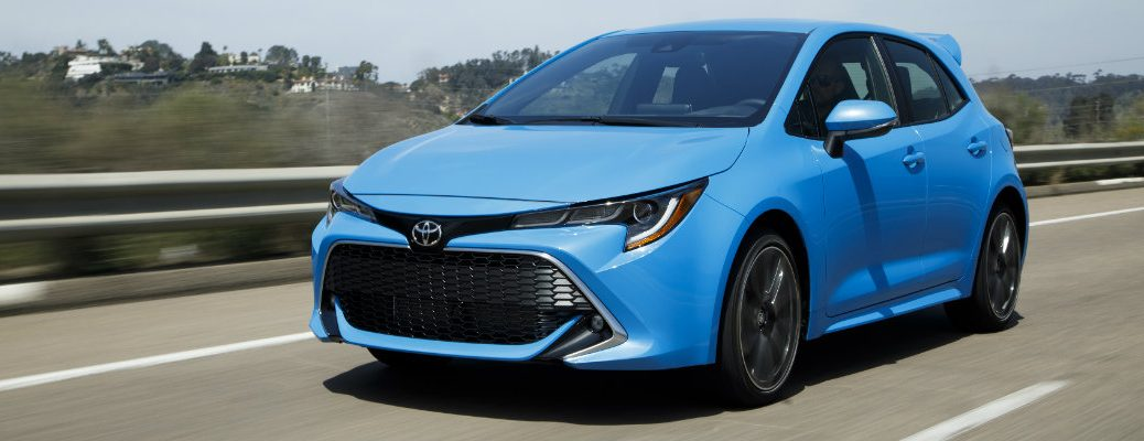 Long view of front of 2019 Toyota Corolla Hatchback driving on empty highway