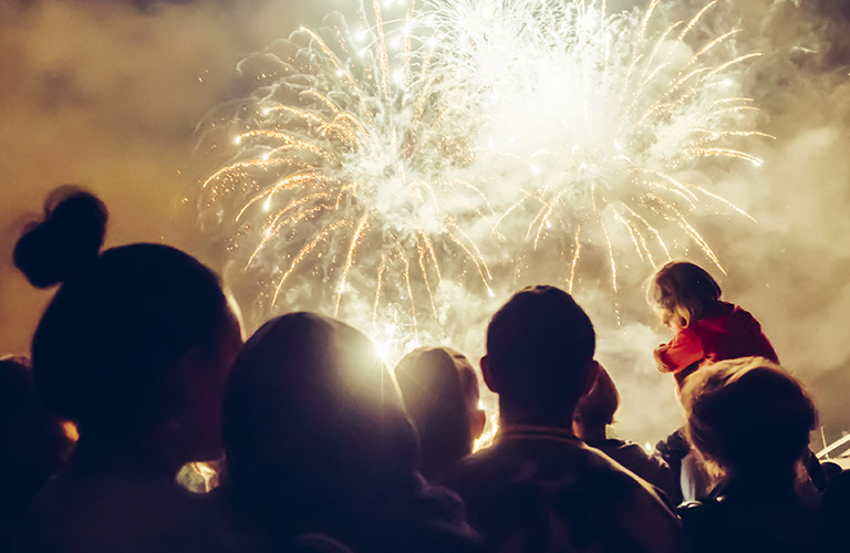People watching a fireworks show at night