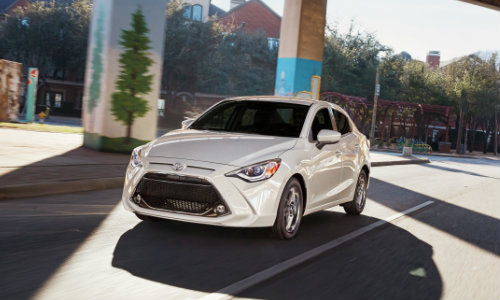White 2019 Toyota Yaris driving under bridge with graffiti on pillars