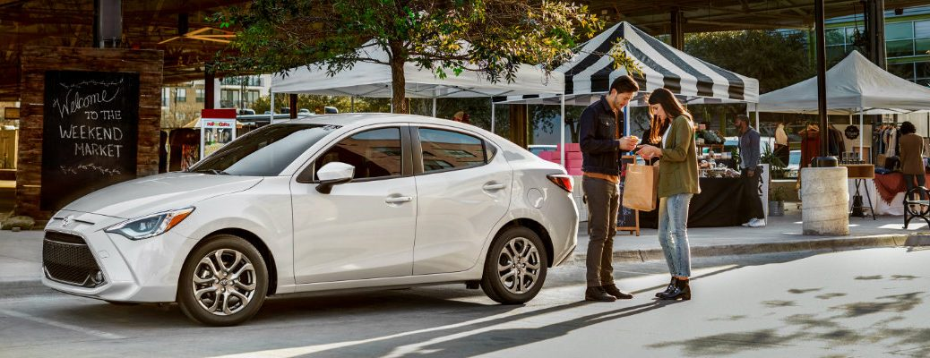White 2019 Toyota Yaris parked in front of marketplace