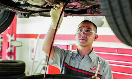 Toyota mechanic draining oil from vehicle