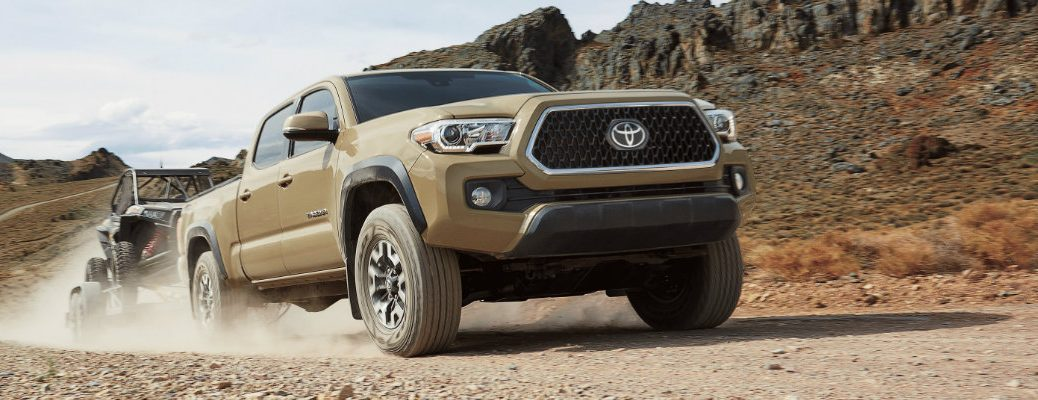 Tan Toyota Tacoma driving on desert road