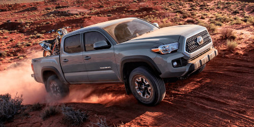 Profile view of 2018 Toyota Tacoma driving on rocky terrain