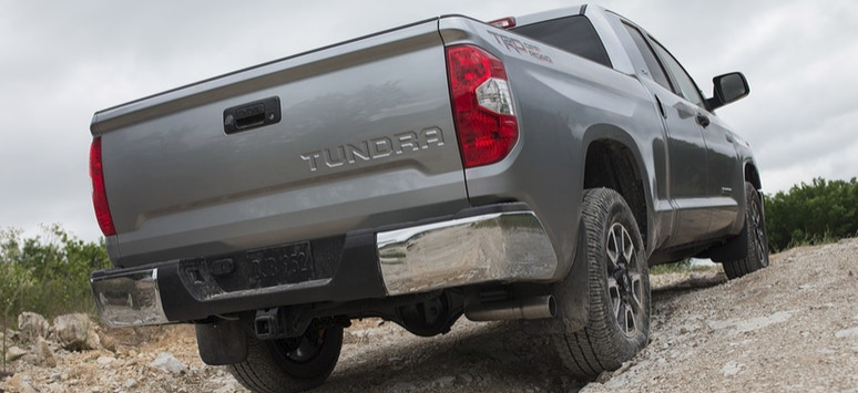 Rear shot of 2019 Toyota Tundra driving through dirt