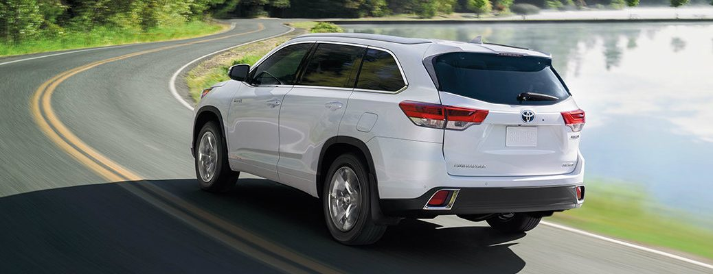 Rear shot of white 2019 Toyota Highlander driving by waterfront