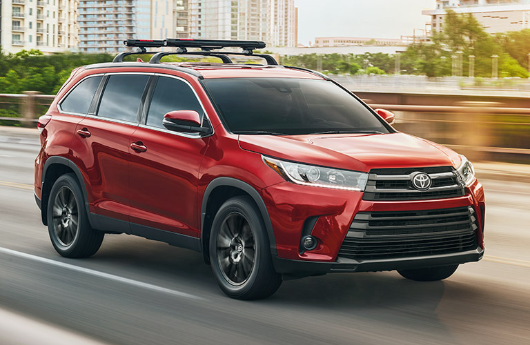 Red 2019 Toyota Highlander driving through city