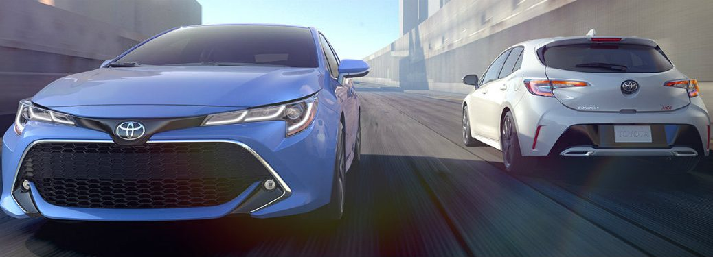 Blue and white 2019 Toyota Corolla Hatchback driving on city road