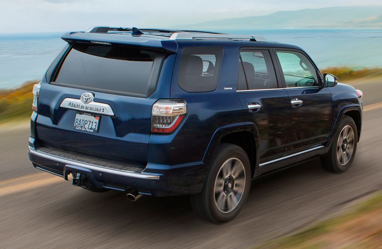Rear shot of blue 2019 Toyota 4Runner driving on waterfront road