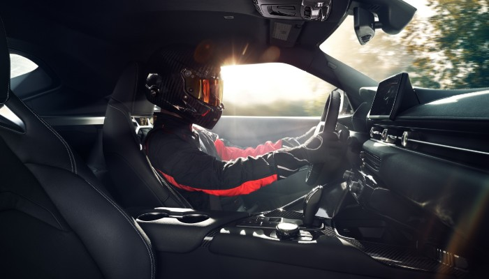 Man in racing gear test driving 2020 Toyota Supra