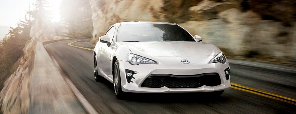 White 2019 Toyota 86 driving on winding mountainous road next to rocks