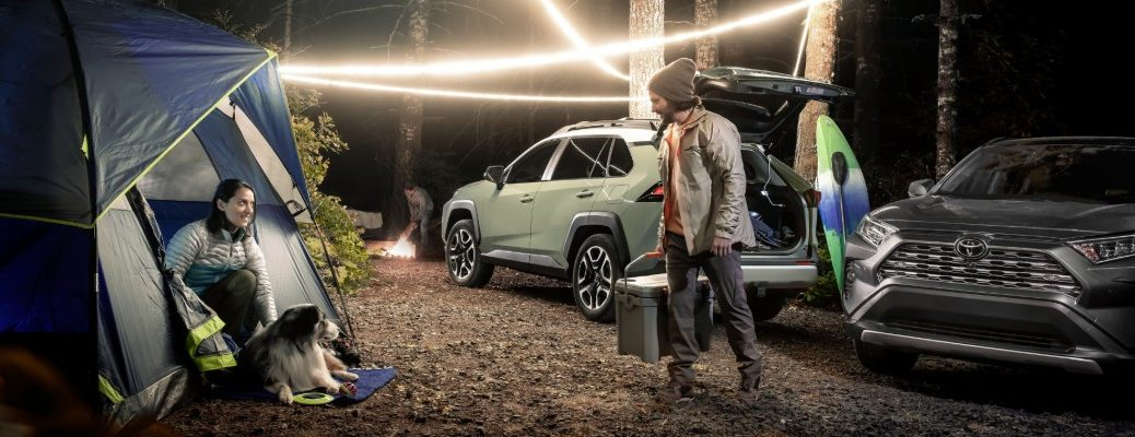 couple camping with two RAV4sin the background