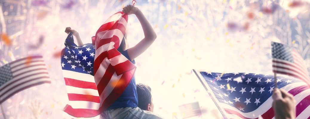 Child holding American flag while sitting on parent's shoulders