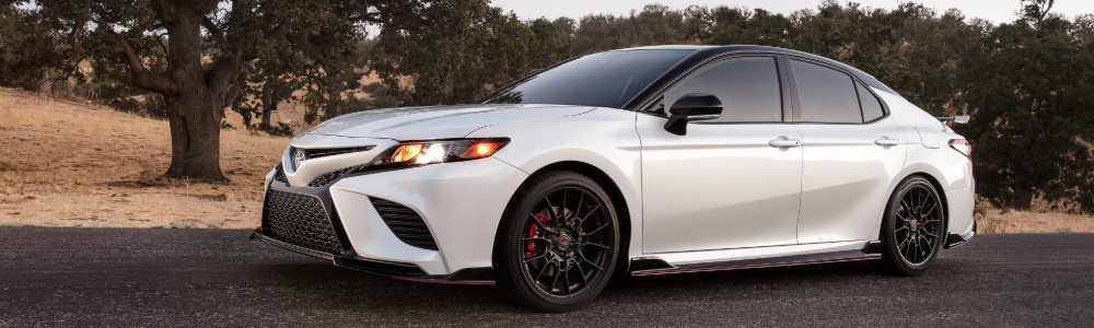 White 2020 Toyota Camry TRD driving at dusk