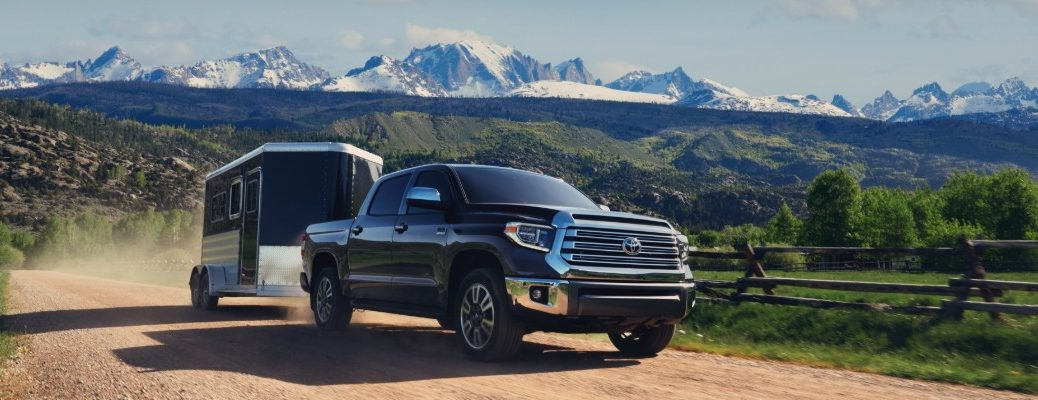 2020 Toyota Tundra towing trailer on dirt road with mountains in background