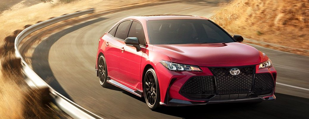 Red 2020 Toyota Avalon driving on mountain road