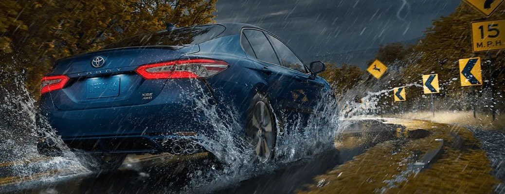 Exterior view of the rear of a 2020 Toyota Camry AWD driving in the rain