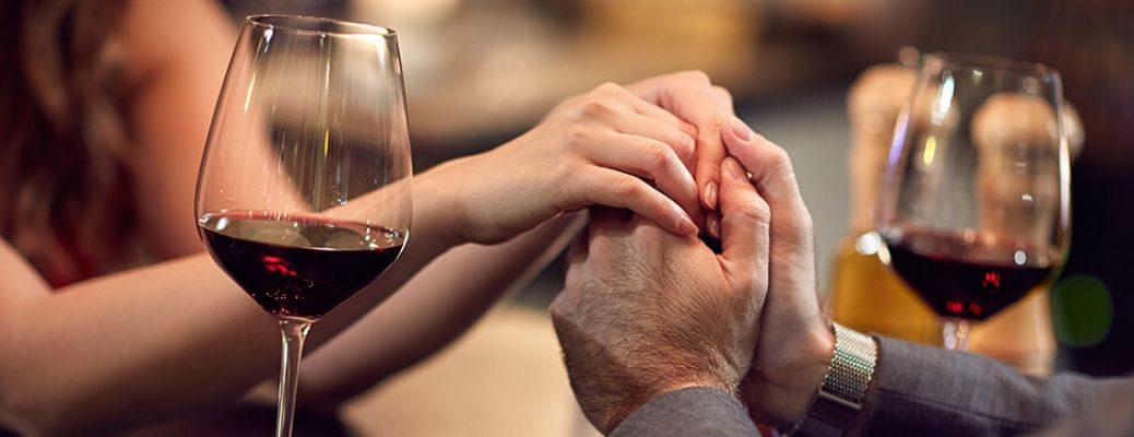 Image of a couple holding hands while enjoying wine at a Valentine's Day dinner