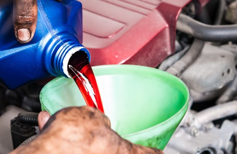 Image of someone pouring transmission fluid into their vehicle