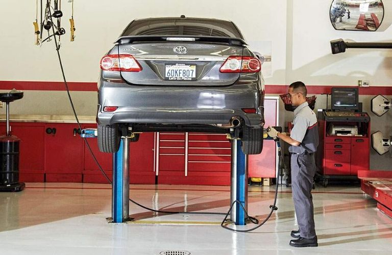 Image of a Toyota service tech working on the tires of a lifted Toyota vehicle