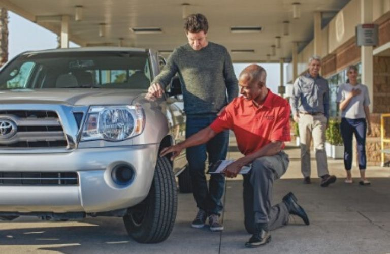 Image of a Toyota service tech walking a customer though the multi-point inspection issues