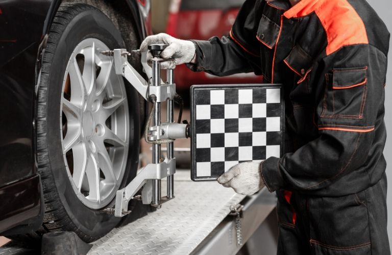 Image of a service technician adjusting the wheel alignment of a vehicle
