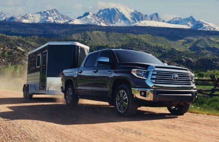 Exterior view of a black 2020 Toyota Tundra towing a horse trailer