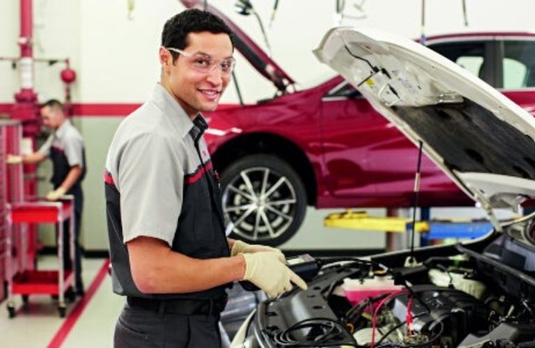 Image of a Toyota service technician checking the oil in a Toyota